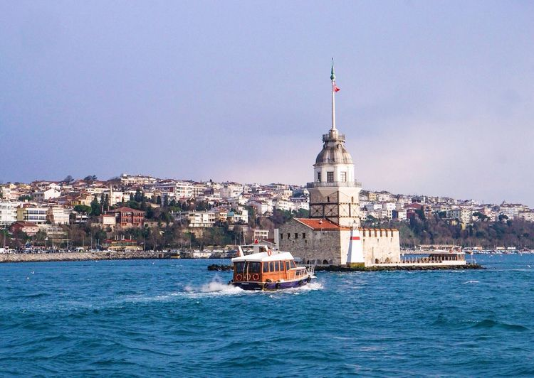 Boat in bosphorus strait by maiden tower against sky