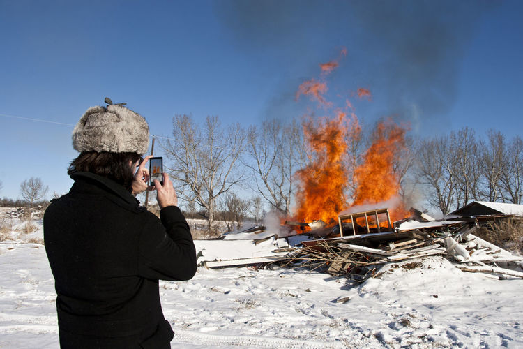 we made fire. Burning Burnpit Casual Clothing Cell Phone  Cell Phone Photography Cloud - Sky Cold Temperature Covering Day Fire Landscape Man Nature Non-urban Scene Outdoors Photographing Photographing The Photographer Scenics Season  Sky Snow Tree Warm Clothing Weather Winter