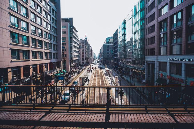 Footbridge in city against clear sky