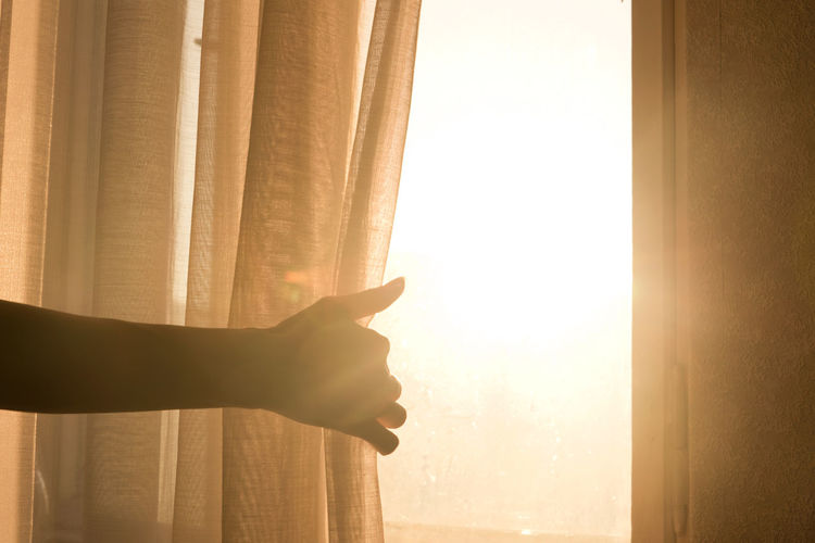Cropped Hand Holding Curtain On Window