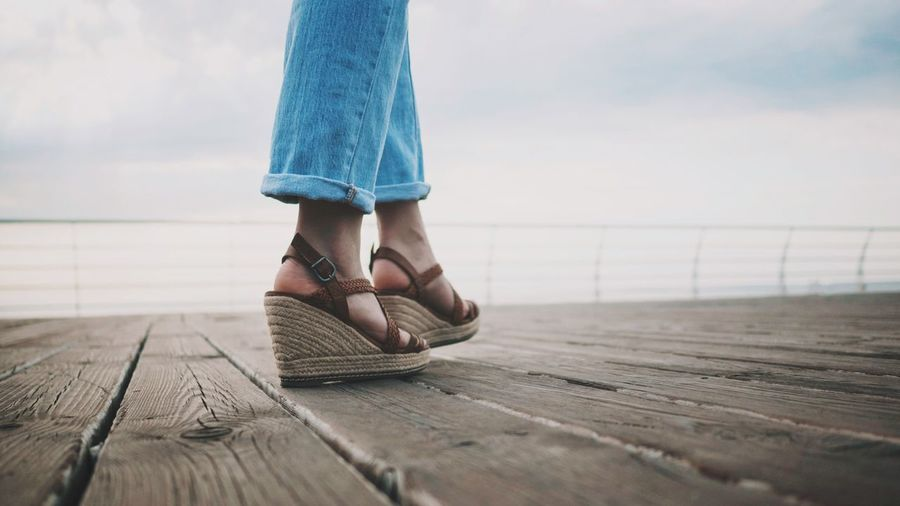 Low Section Of Woman Wearing Sandals Walking On Pier Against Sky