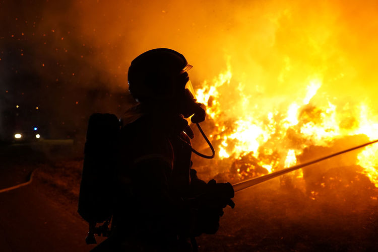 Silhouette firefighter extinguishing fire at night
