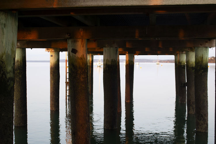 Architecture Beach Below Bridge Bridge - Man Made Structure Built Structure Colonnade Connection Day In A Row Jetty Nature No People Outdoors Pier Reflection Sea Sunset Underneath Water Waterfront Wood - Material Wooden Post