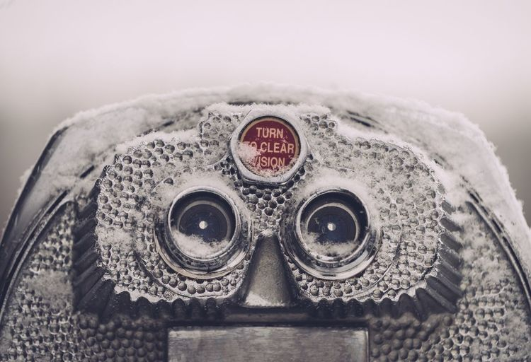 Close-up of coin-operated binoculars against white background