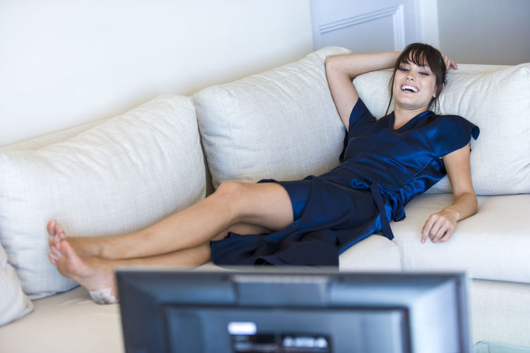 Laughing Woman Watching Television While Lying Down On Sofa At Home