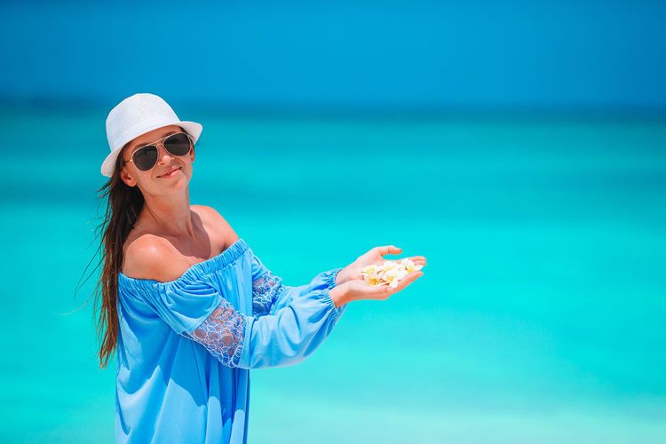 Young woman wearing sunglasses standing against blue sea