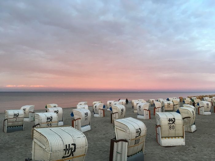 Hooded Chairs On Beach Against Cloudy Sky