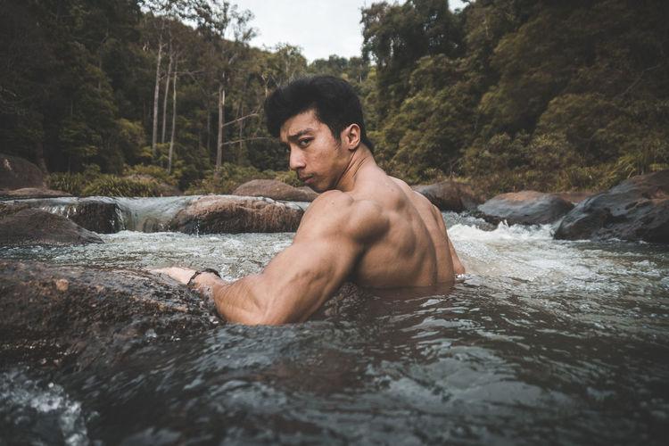 Portrait of muscular shirtless man in stream