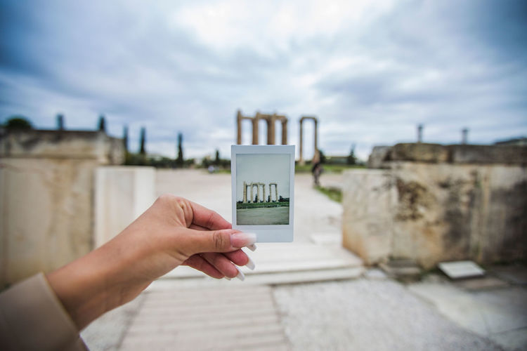 Cropped woman holding photograph at olympian zeus temple against cloudy sky