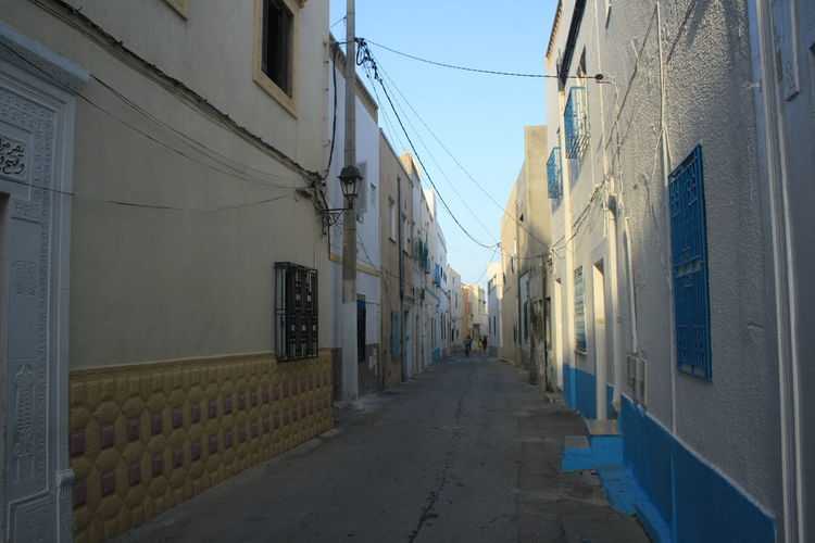 Alley Architecture Blue Building Exterior Built Structure Cable Clear Sky Day Diminishing Perspective Footpath Long Narrow Power Line  Residential Building Residential Structure The Way Forward Walkway