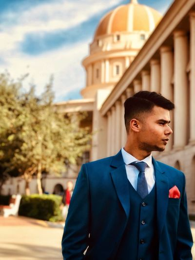 Young man looking away while standing against built structure