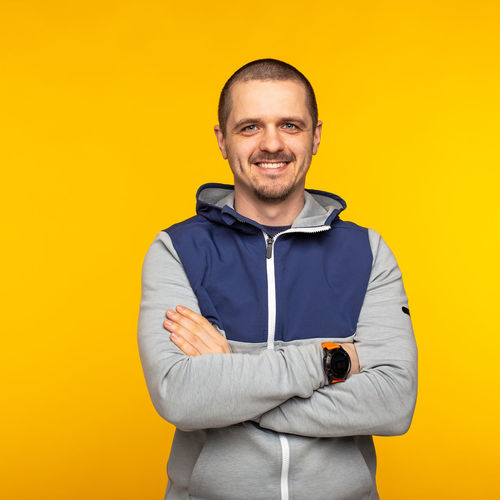 Man standing in hoodie and looking in camera and smiling at orange or yellow background Looking At Camera Smiling Portrait Studio Shot One Person Happiness Yellow Front View Standing Colored Background Arms Crossed Emotion Waist Up Adult Men Clothing Indoors  Toothy Smile Yellow Background Freelancer Man Males  Hoodie