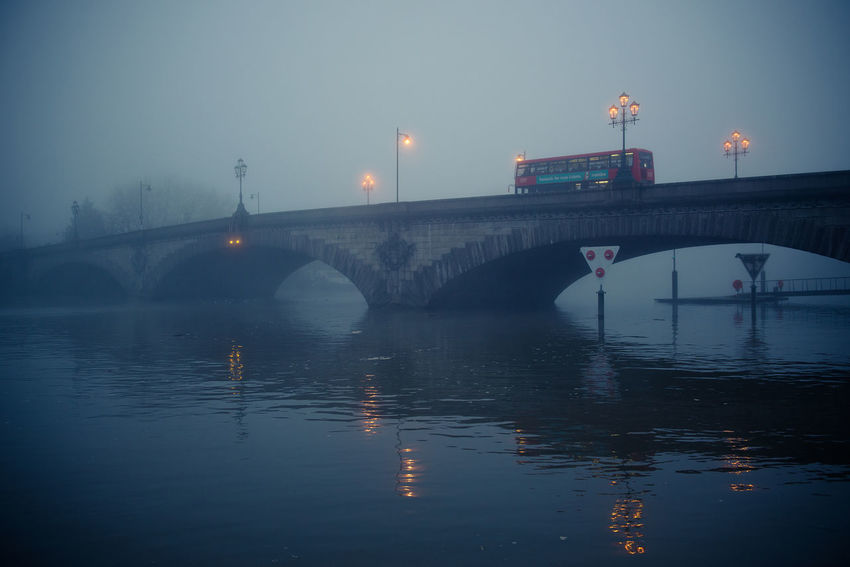 Bridge Bridge - Man Made Structure Fog Foggy Day Foggy Evening Gloomy Gloomy Weather Illuminated Kew Bridge London Outdoors Reflection River Street Light Thames Thames River Water Double Decker Bus Double Decker Red Bus London Bus Miles Away