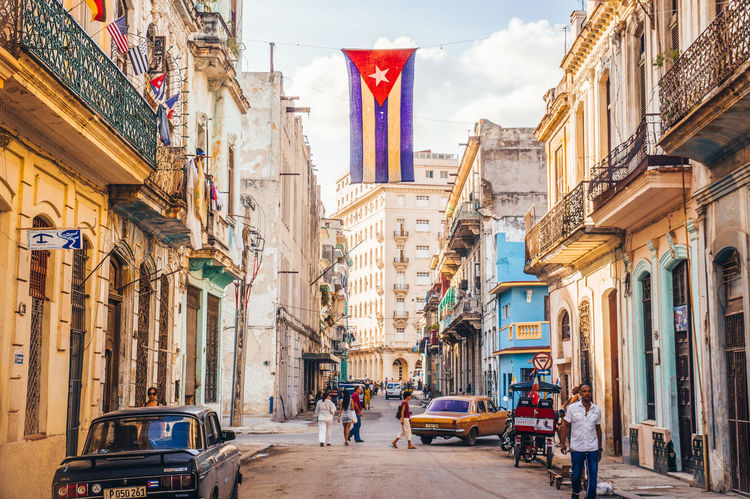 Havana, Cuba in December 2015: A Cuban flag with holes waves over a street in Central Havana. La Habana, as the locals call it, is the capital city of Cuba Architecture Building Exterior City Cityscape Communism Cuba Cuba Collection Cuban Cuban Cars Cuban Flag Day Flag Flags Havanna La Habana Motion Old Buildings Oldtown Outdoors Patriotism People Revolution Socialism Street Travel Destinations