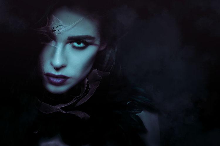 Portrait Of Woman Wearing Spooky Make-Up In Darkroom