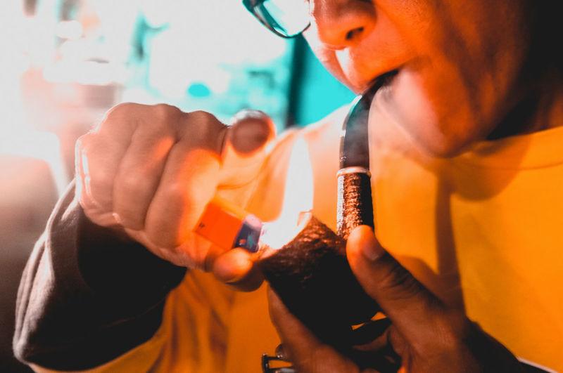 Midsection Of Man Burning Smoking Pipe