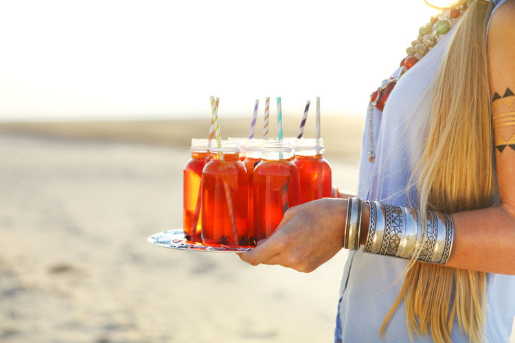 Midsection of woman holding drink at beach against sky