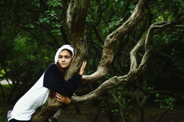 Young Woman Wearing Panda Costume Embracing Tree At Forest