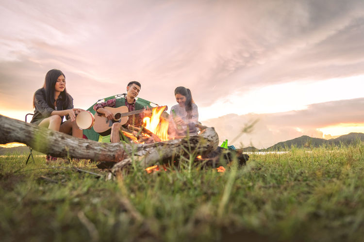 Friends Camping On Grassy Field Against Sky During Sunset