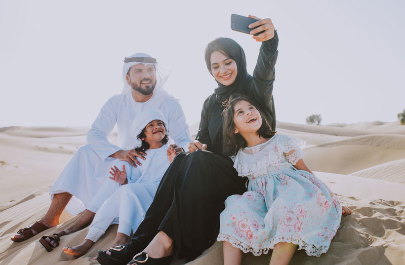 Young woman photographing family with phone at desert