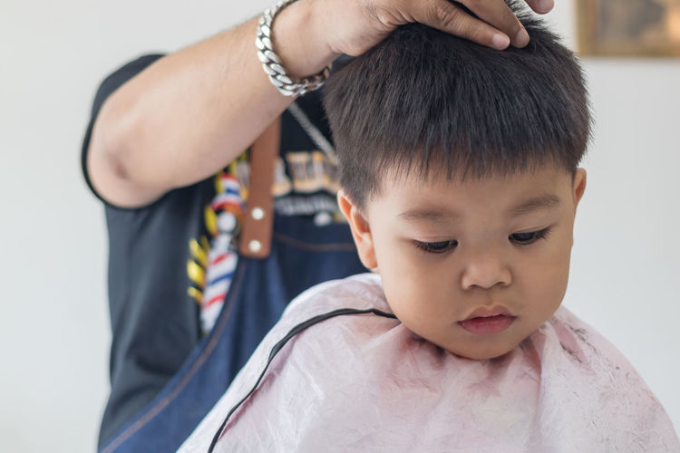 Midsection of barber cutting boy hair in salon