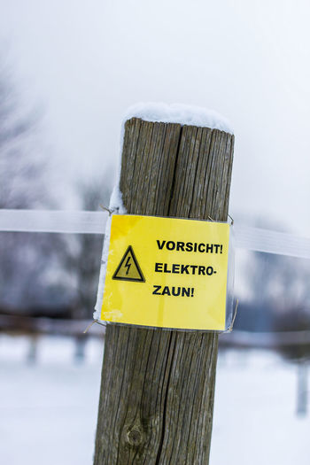 Close-up of sign on wooden post during winter