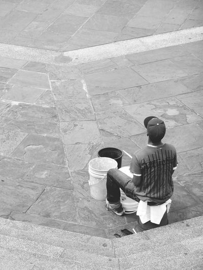 Rear view of a man sitting with buckets on road