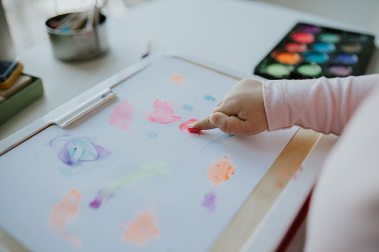 Midsection of child holding multi colored pencils on table