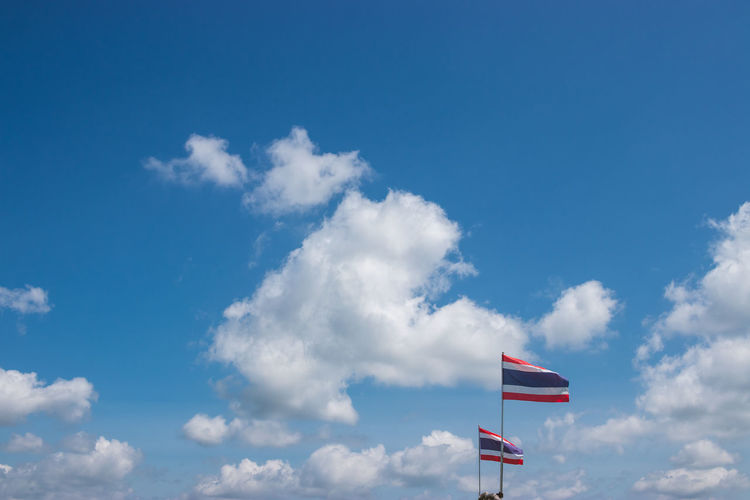 Sky Cloud - Sky Low Angle View Day Flag Patriotism Nature Blue No People Outdoors Beauty In Nature Wind Environment Sunlight White Color Pride Motion