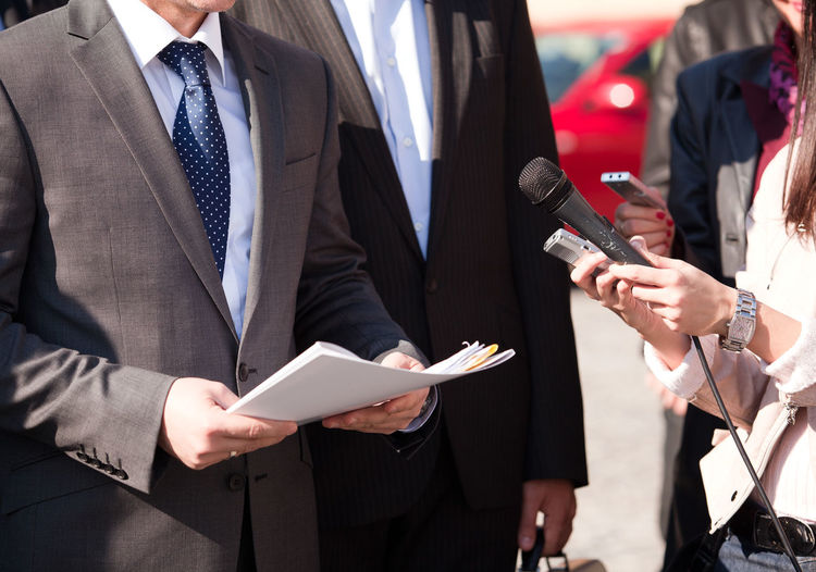 Midsection of journalist holding microphone in front of businessmen