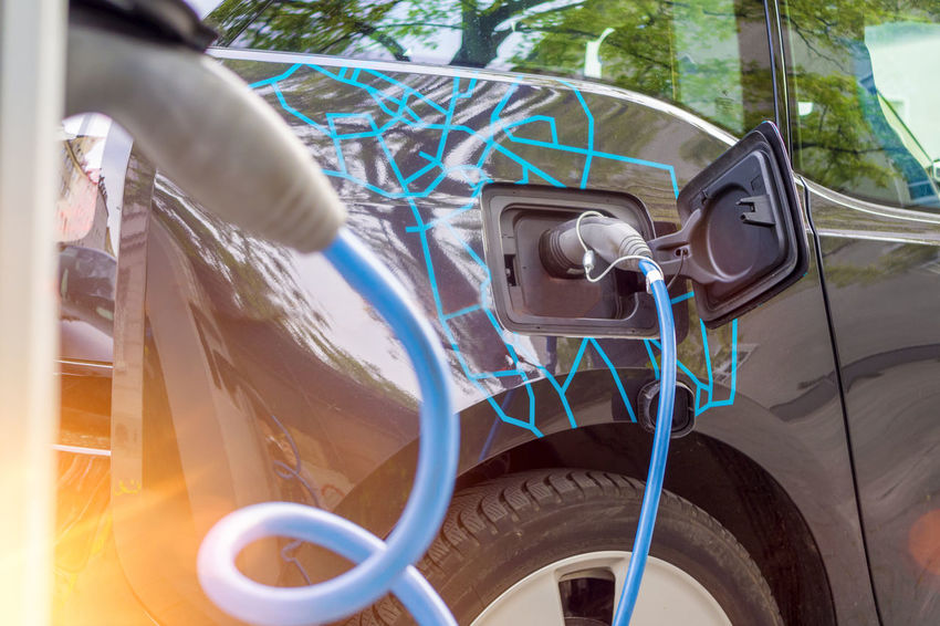 Close up of the power supply plugged into an electric car being charged Automotive Cable Car Charge Charging City Close Up Close-up Concept E-car Electric Car Green Hybrid Infrastructure Lifestyle Modern Parking Plug Power Supply Renewable Energy Station Technology Unfiltered Urban Vehicle