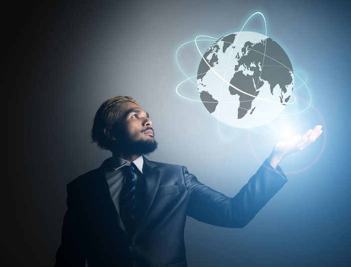 Digital composite image of businessman holding globe against colored background