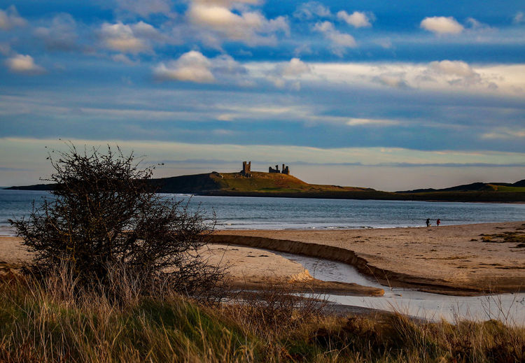 Channel to the sea Dunstanburgh Castle Architecture Beach Beauty In Nature Building Exterior Built Structure Castle Ruin Cloud - Sky Day Grass History Nature No People Outdoors Sand Scenics Sea Sky Tourism Tranquility Travel Travel Destinations Vacations Water