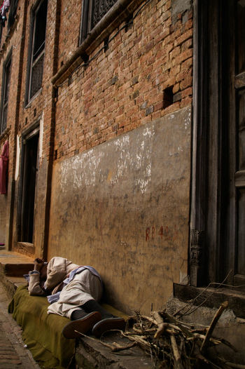 Man sleeping on wall of abandoned building