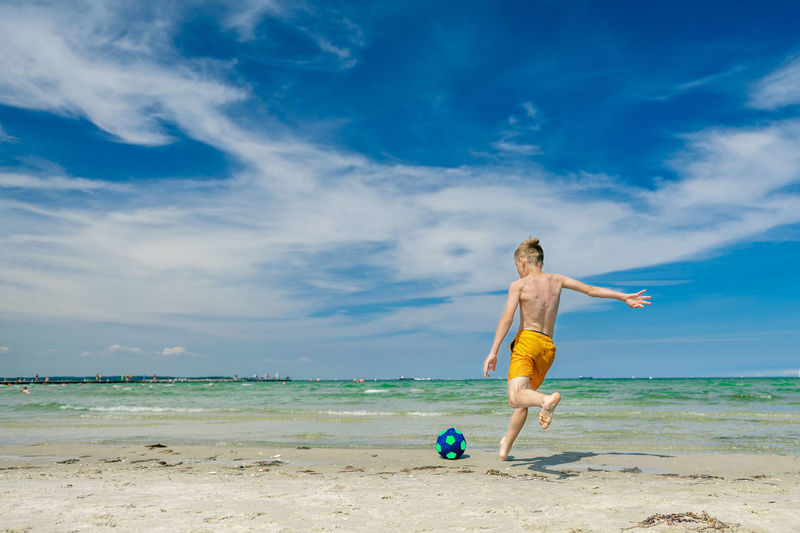 Full length of shirtless man on beach