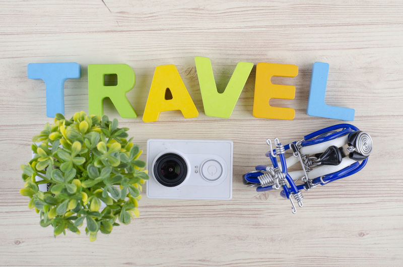 top view vacation and holiday concept word TRAVEL with accessories on wooden background Wood - Material Text Capital Letter Table Indoors  Still Life Directly Above Western Script No People Alphabet Letter Communication Toy Yellow Medium Group Of Objects Blue High Angle View Toy Block Single Word Group Of Objects