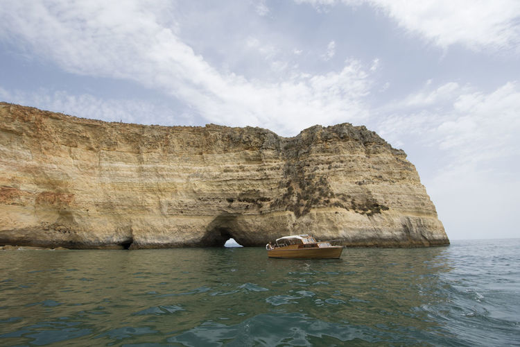 The Algarve Coast Cliffs Cloud Coastline Portugal Albufeira Beauty Beauty In Nature Boat Cave Cliff Coast Day Europe Nature Outdoors Sea Sky Tourism Travel Destinations Water