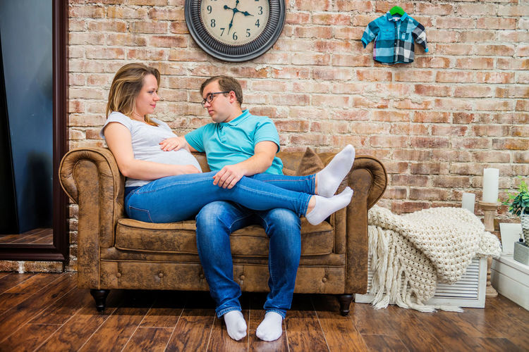 Beautiful pregnant woman and man sitting near brick wall Pregnant Woman Adult Brick Wall Cheerful Clock Couple - Relationship Domestic Life Family Females Full Length Indoors  Males  Married Men Pregnancy Pregnant Pregnant Belly  Pregnant Life Pregnant Phtography Relaxation Sitting Togetherness Women Young Adult Young Couple