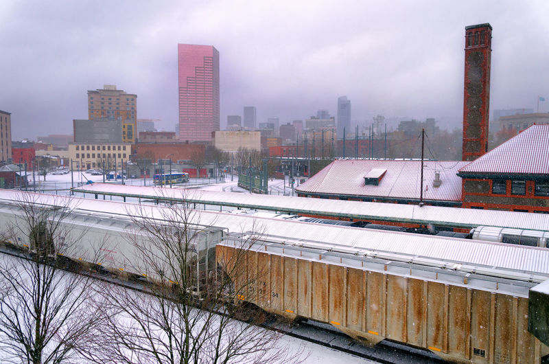 Freight Train In City Against Cloudy Sky During Winter