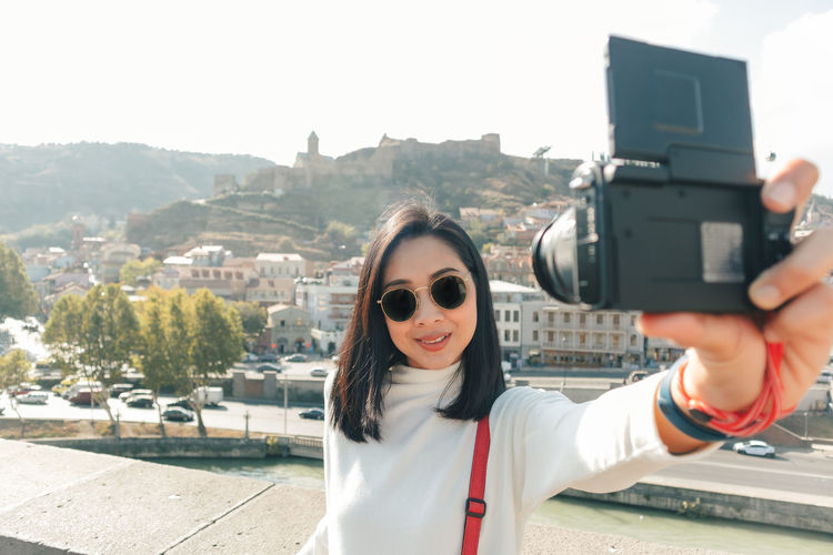 Portrait of young woman photographing cityscape
