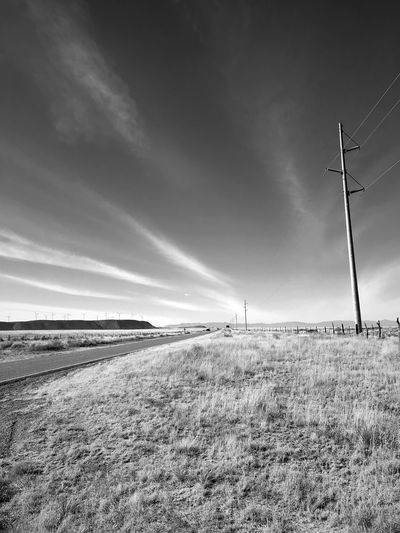 """Power Poles To Windmills"" Across the vast rural area of Central New Mexico bringing dependable power to the scattered population is a challenge answered by a variety of sources from wind, solar and traditional power poles. Power Poles Power Lines New Mexico Photography New Mexico Black And White Photography Black And White Blackandwhite Field Sky Outdoors Nature No People Tranquil Scene Day Grass Scenics Landscape Industrial Windmill"