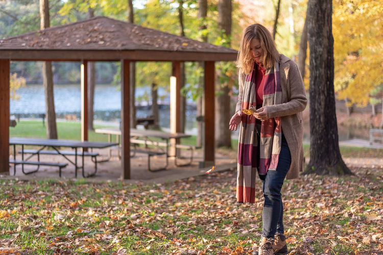 Full length of woman holding autumn tree