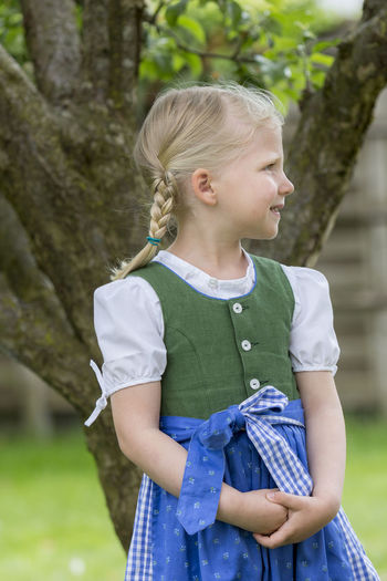 Cute girl looking away while standing against tree trunk
