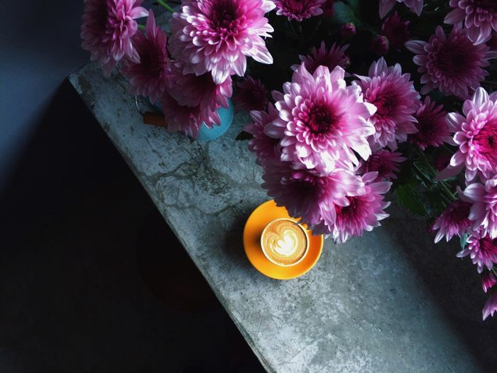 Flower vase with coffee on table at home