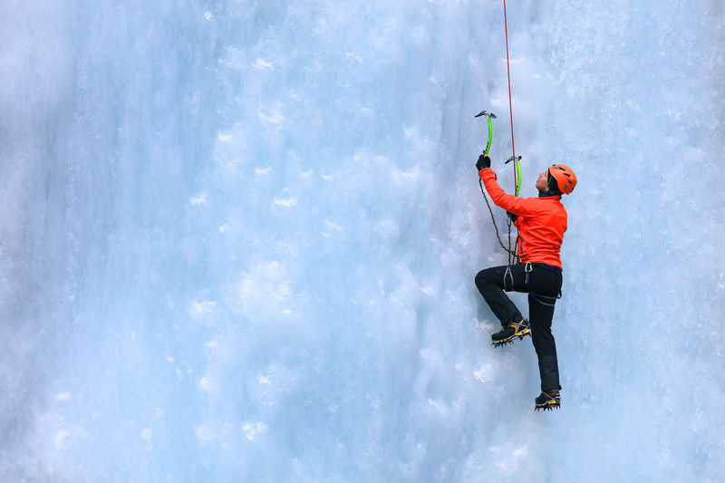 Side view of woman ice climbing