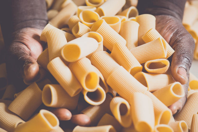 Close-Up Of Hands Holding Fresh Pasta In Factory