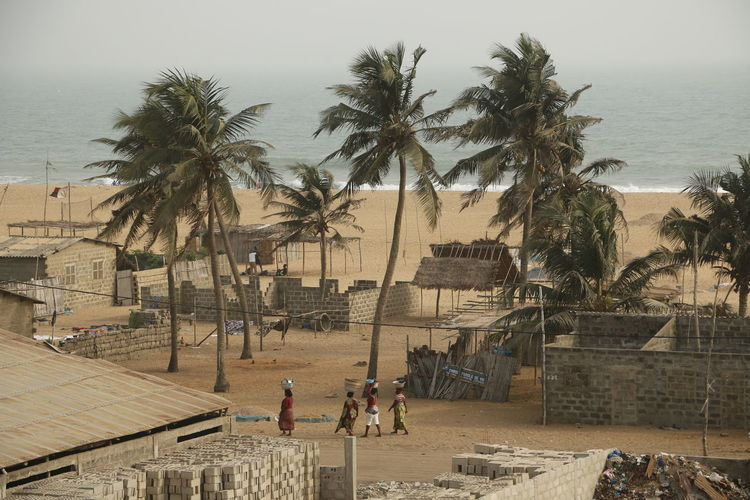 Outside of Cotonou you can find fishing villages at the beach, African life African Benin Cotonou Fishing Village Africa African Beauty Architecture Beach Beauty In Nature Building Exterior Built Structure Day Leisure Activity Lifestyles Nature Outdoors Palm Tree People Sea Sky Tree Walking Women