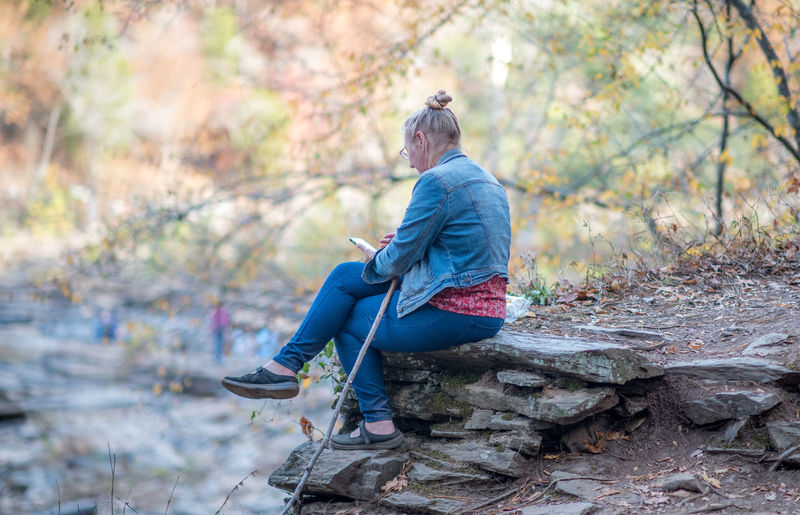 Woman sitting on rock reading a book. Georgia Lithia Springs, GA Reading Woman Autumn Book Cane Casual Clothing Forest Leisure Activity One Person Outdoors Real People Rock Rock - Object Sitting Sweetwater Creek