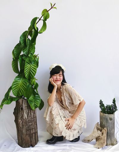 Portrait of young woman standing against plants
