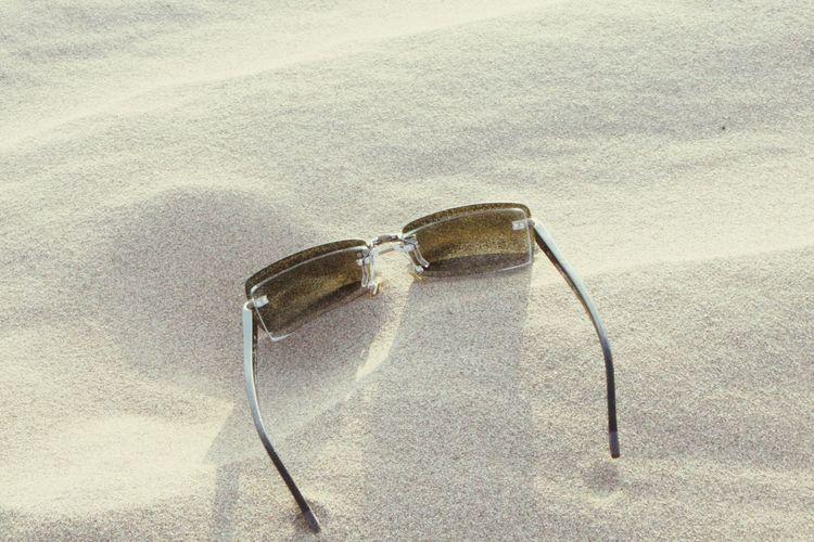 High angle view of eyeglasses on sand